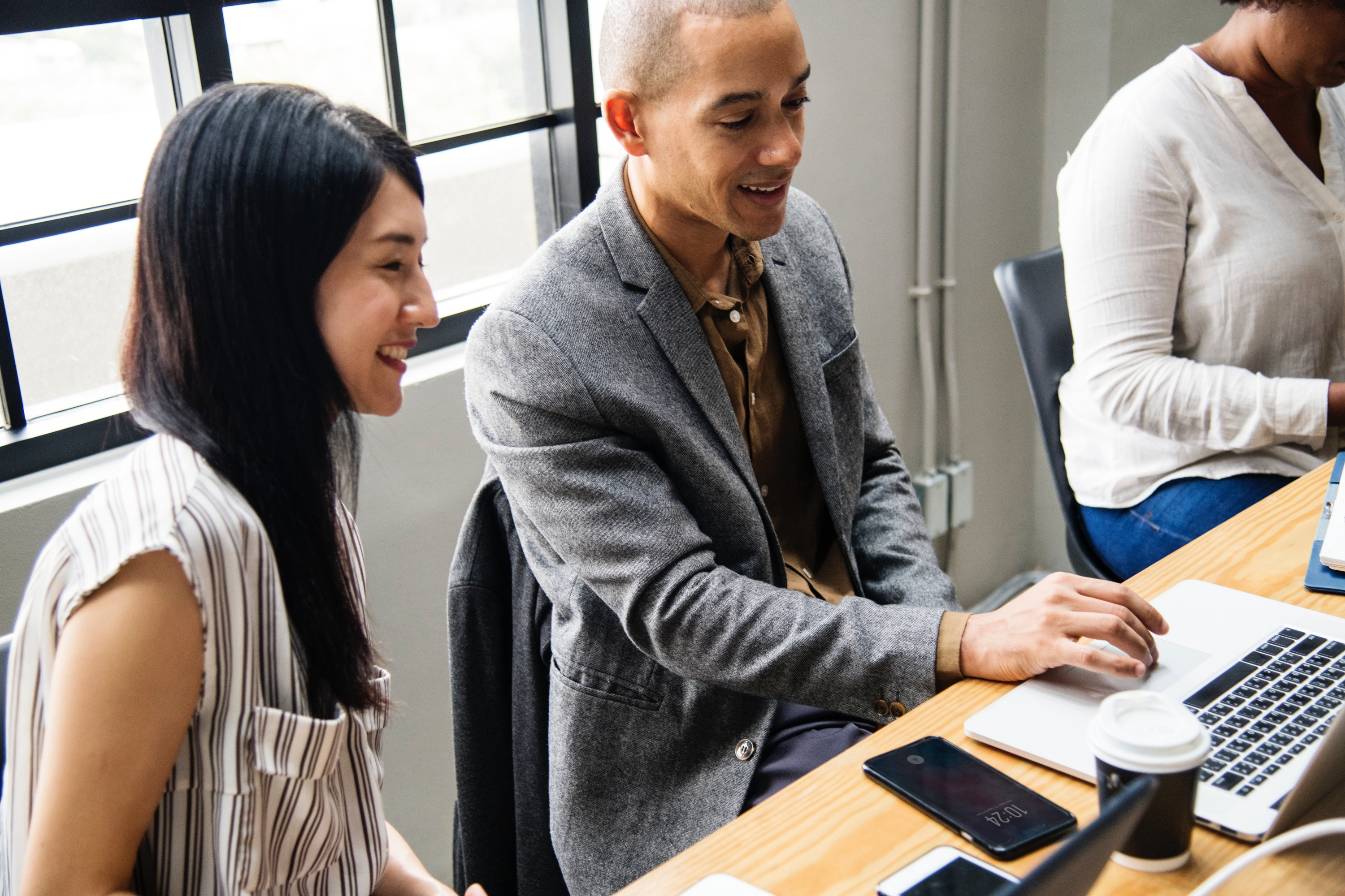 Young man and woman smiling at a computer in an office