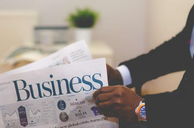Man opening a business newspaper