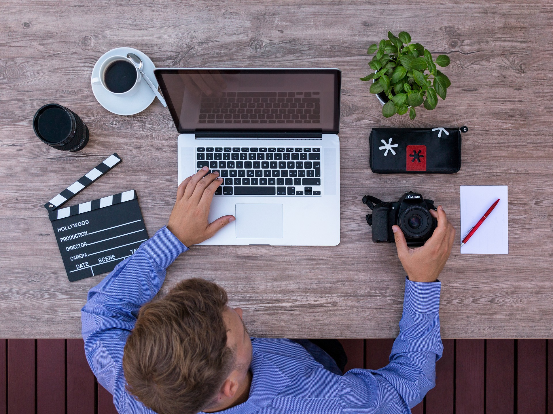 Video producer working at a laptop with a clapboard and DSLR camera nearby