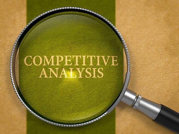 Magnifying glass over the words competitive analysis