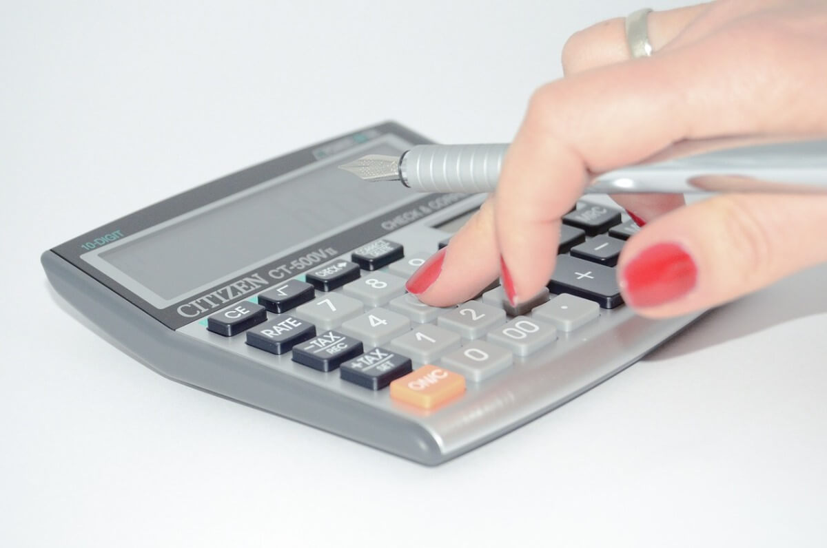 Woman's hand using a calculator to figure out the cost of hiring employees