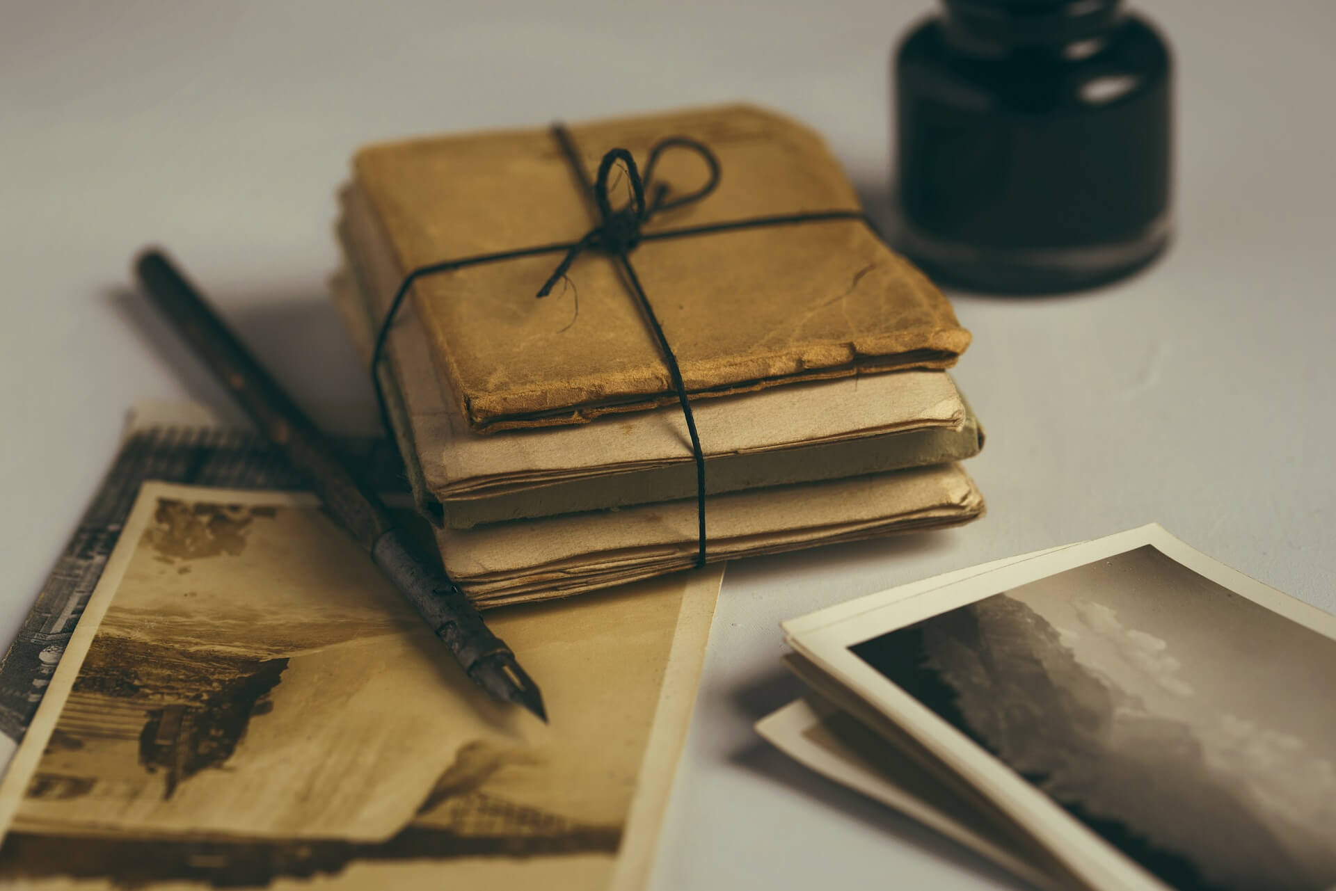 Shot of a quill, photographs and bundled papers