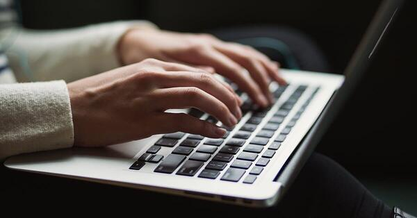 Person writing a blog on a laptop while paying attention to long-tail keywords and buyer personas to increase audience engagement.