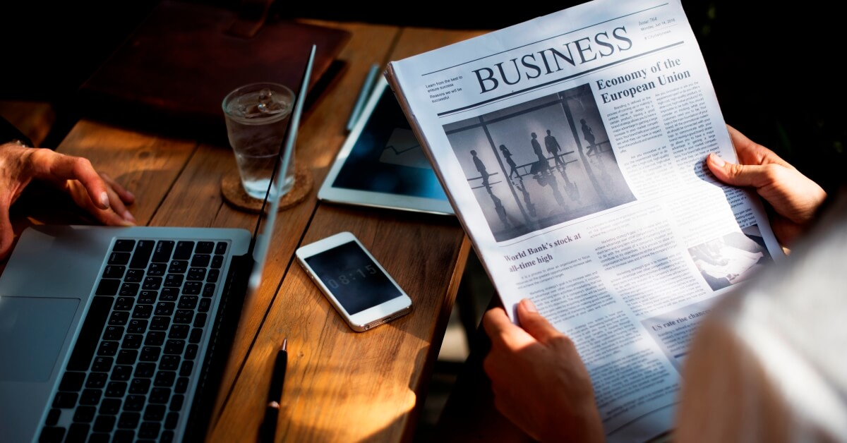 Image of person reading the business section of a newspaper, representing how whitespace and visual structure can make reading important text more appealing.