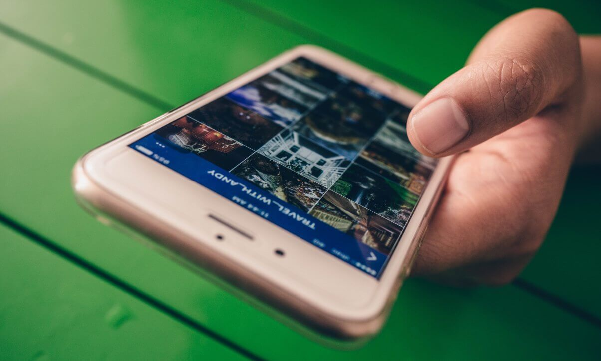 Image of a hand holding a smartphone with a photo gallery to represent using visuals in your blog posts.