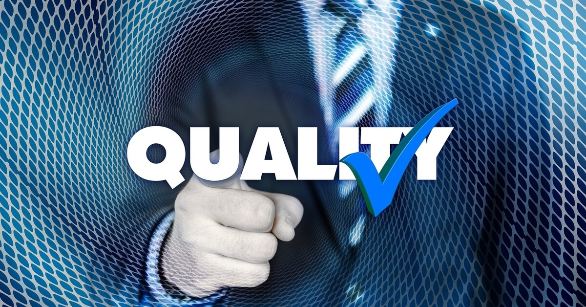 A man in a suit points with the word quality and a checkmark superimposed on the photo