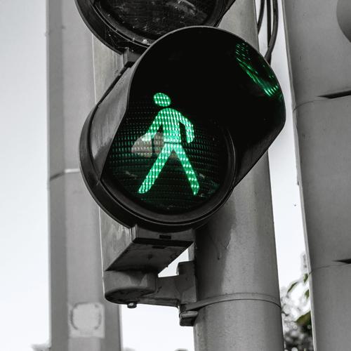 Illuminated green man on traffic light