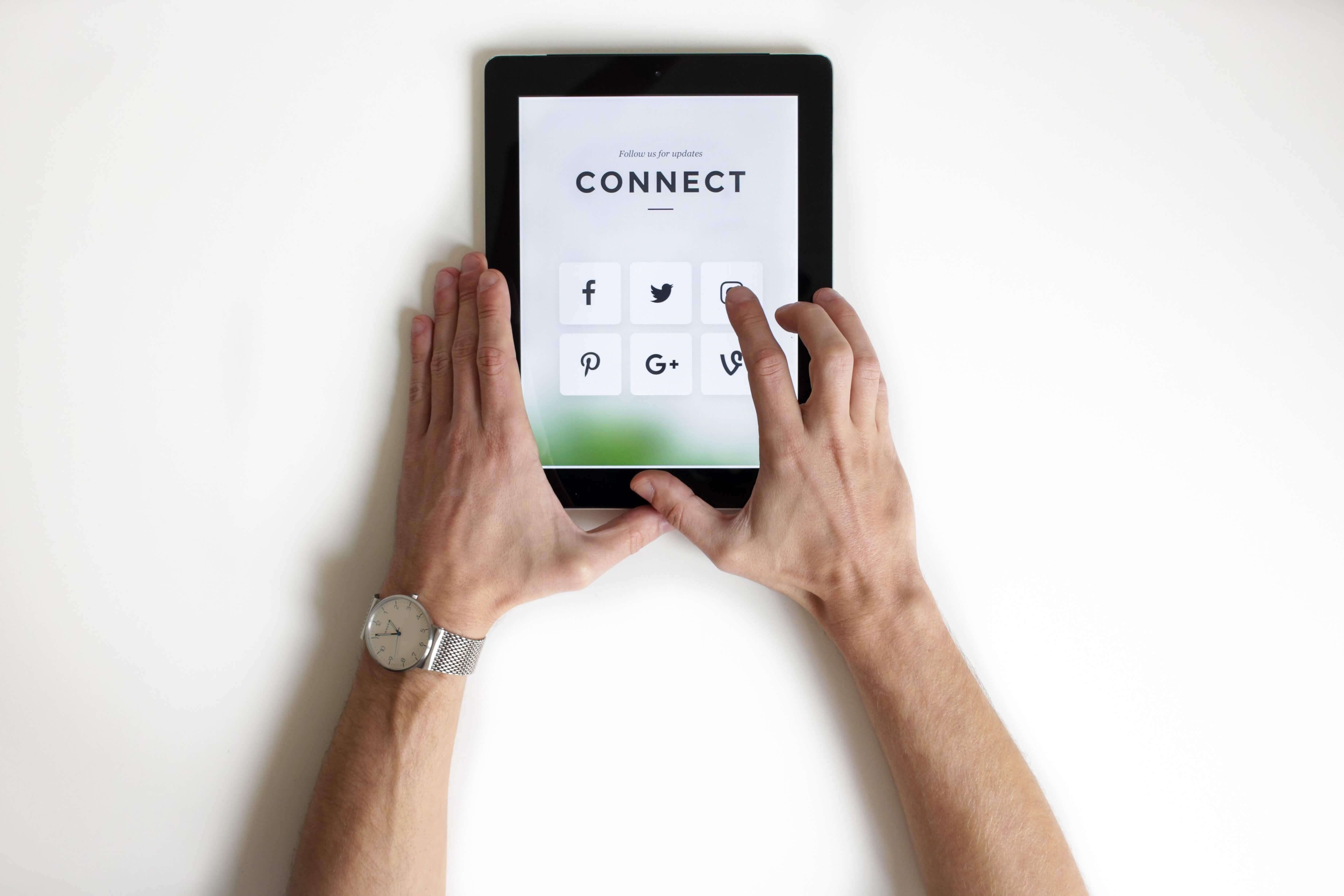 Man pressing a social media button on a tablet