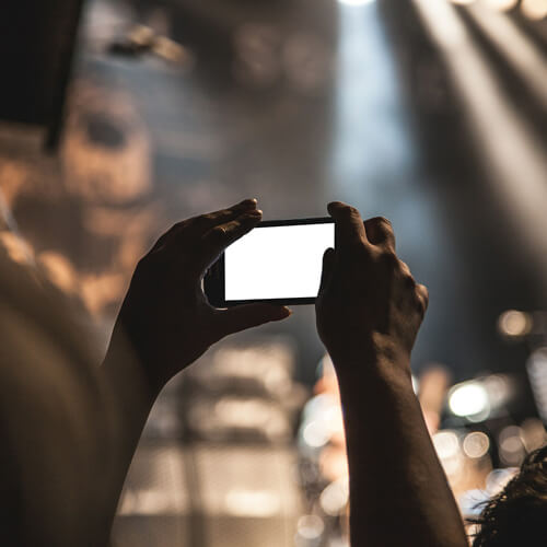 Person holding up a smartphone at a concert