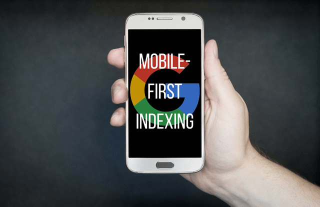 Photo of a hand holding a cell phone with a Google logo and the words mobile-first indexing